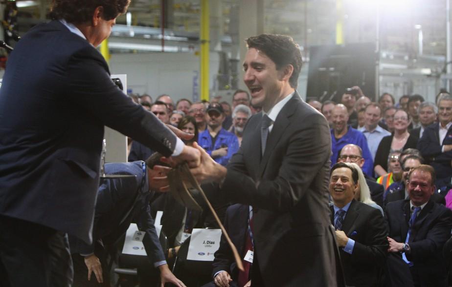 Le premier minstre Justin Trudeau a reçu en cadeau une cravate des mains de Jerry Dias, président d'Unifor, le syndicat des travailleurs de l'automobile du Canada, durant une cérémonie à l'usine de moteurs Ford d'Essex, en Ontario. (THE CANADIAN PRESS)