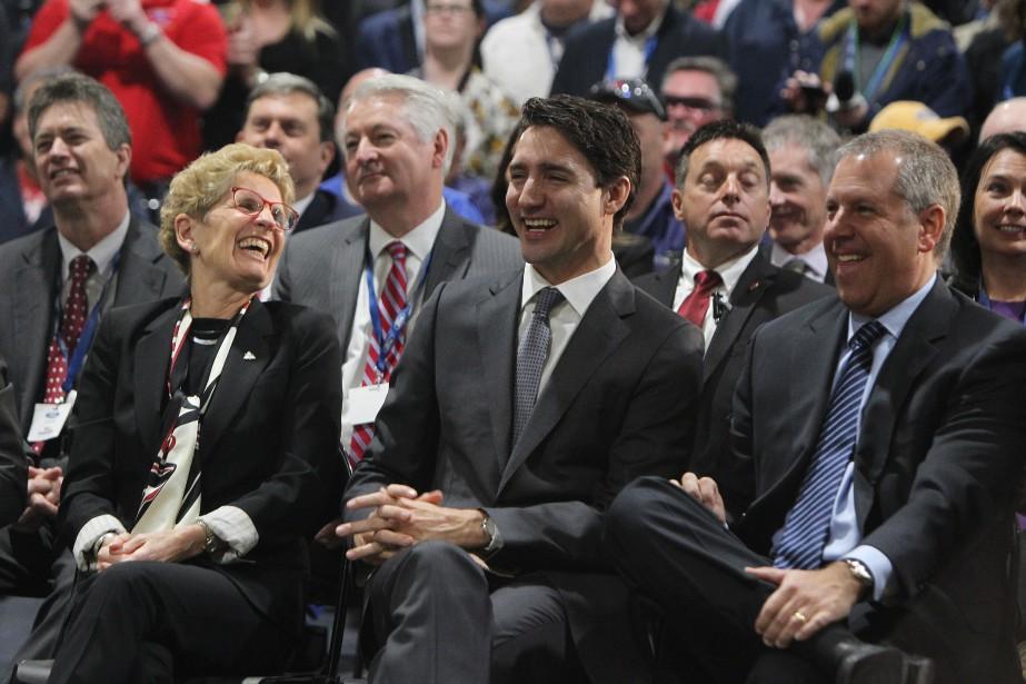 Le premier ministre Justin Trudeau était tout sourire lors de l'annonce en grande pompe d'une subvention de 100 millions de dollars au constructeur américain Ford. On le voit entre la première ministre de l'Ontario, Kathleen Wynne, et le président de Ford of the Americas, Joe Hinrichs, à l'usine de moteurs Ford d'Essex, en Ontario. (THE CANADIAN PRESS)