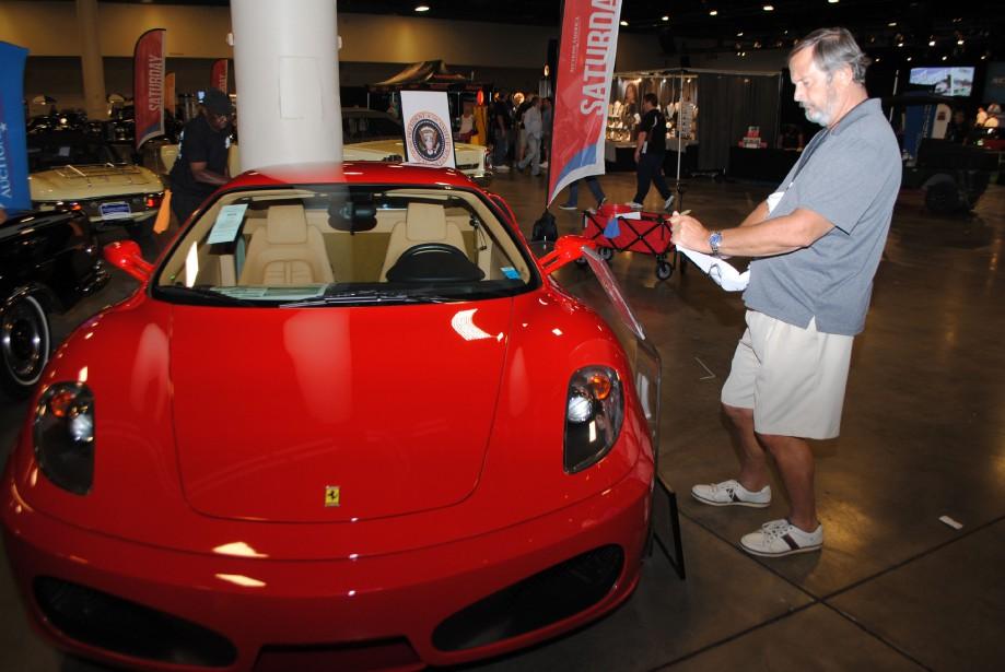 Un homme examine la Ferrari F430 achetée par Donald Trump en 2007dans la salle de montre de la maison d'encan Auctions America à Fort Lauderdale, en Floride. (AFP)
