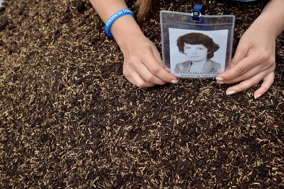 Une femme tient la photo d'une proche disparue... (PHOTO GUILLERMO LEGARIA, ARCHIVES AFP)