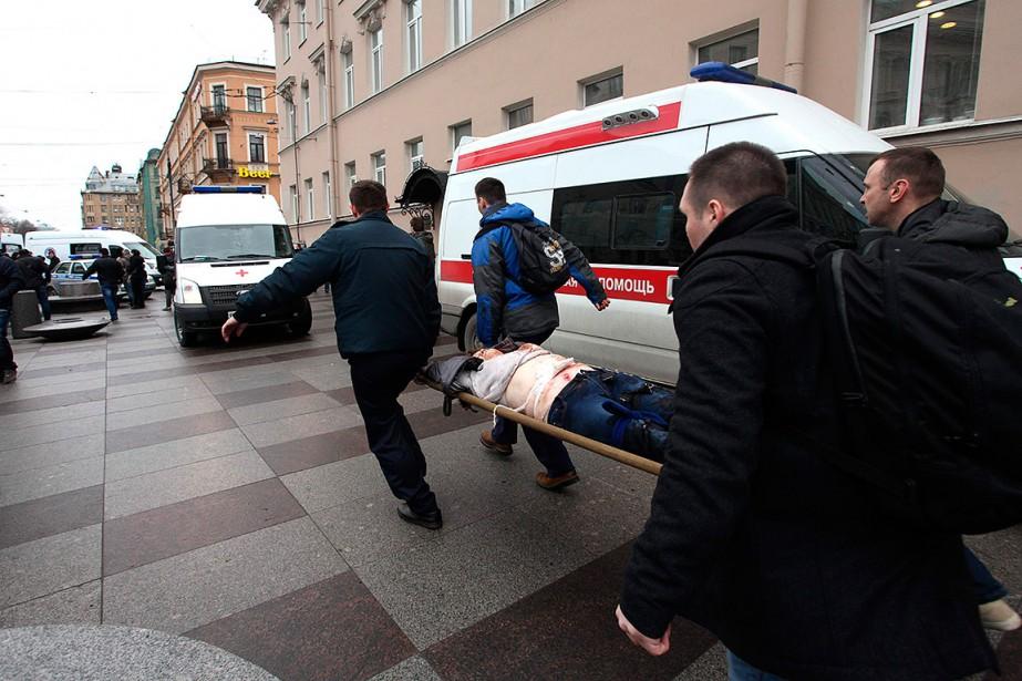 Des hommes transportent un blessé à l'extérieur de la station Tekhnologichesky Institut du métro de Saint-Pétersbourg. (ALEXANDER TARASENKOV, AFP)