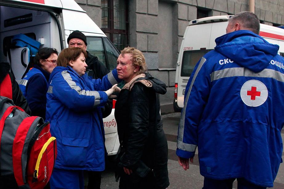 Des ambulanciers aident une femme blessée près de la station de métroTekhnologichesky Institut. (ALEXANDER TARASENKOV, AFP)