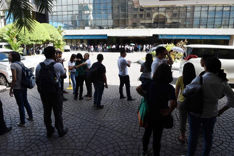 Des employés d'une tour à bureaux de Manille... (PHOTO Ted ALJIBE, AFP)