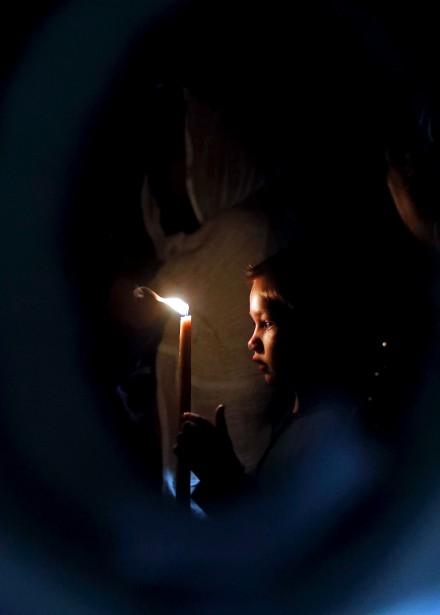 Un enfant tient un cierge, alors qu'il entre dans le Tombeau de Jésus, dans l'Église du Saint Sépulcre, vendredi. | 14 avril 2017
