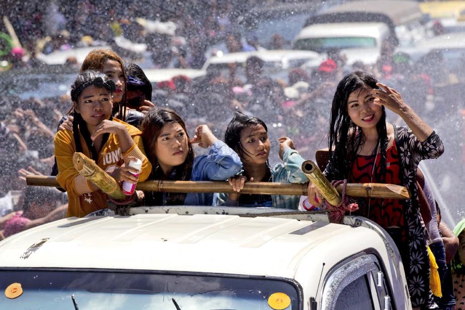 Des fêtards sont aspergés d'eau alors qu'ils circulent à l'arrière d'une camionnette durant la parade pour le festival de l'eau, aussi connu comme le Festival du Nouvel An birman, à Yangon. | 14 avril 2017