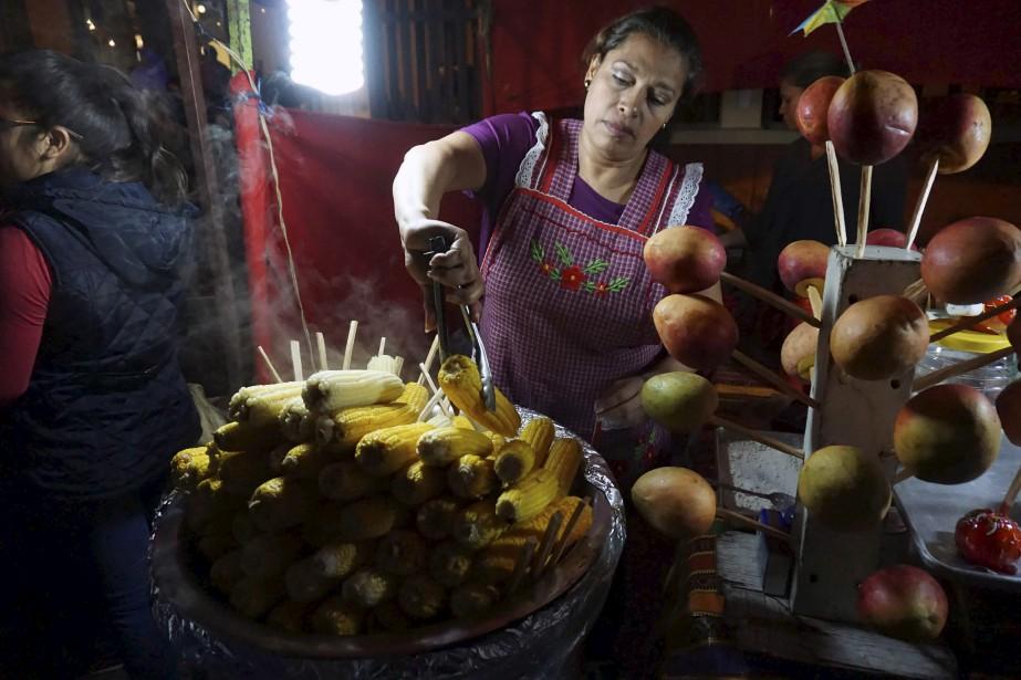 Une femme vend du maïs et des mangues à des participants d'une reproduction de la procession dans le quartier historique de Guatemala. | 14 avril 2017