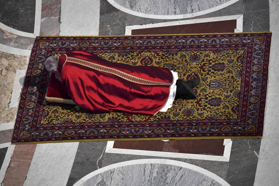 Le pape François s'étend au sol pour prier durant une messe pour célébrer la Passion du Christ, vendredi, à la Basilique Saint-Pierre du Vatican. | 14 avril 2017