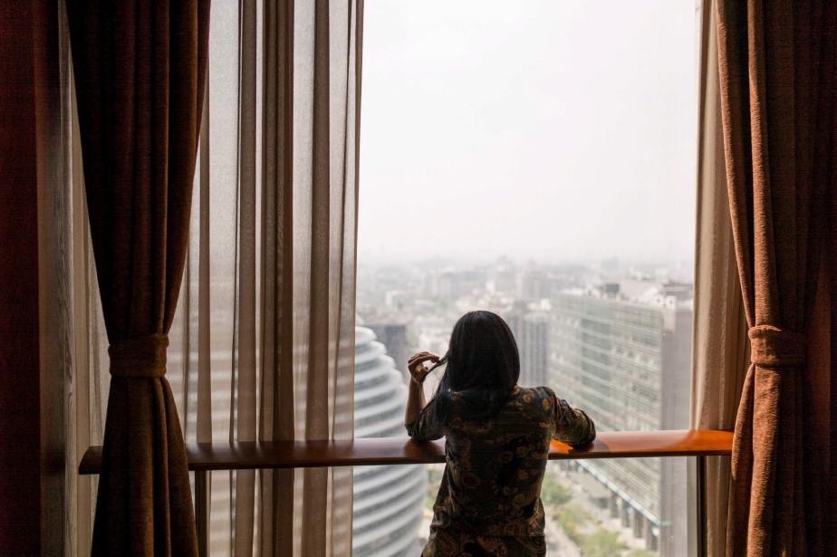Une femme observe l'horizon à travers une fenêtre, à Pékin, alors que le smog enveloppe la métropole chinoise. | 14 avril 2017