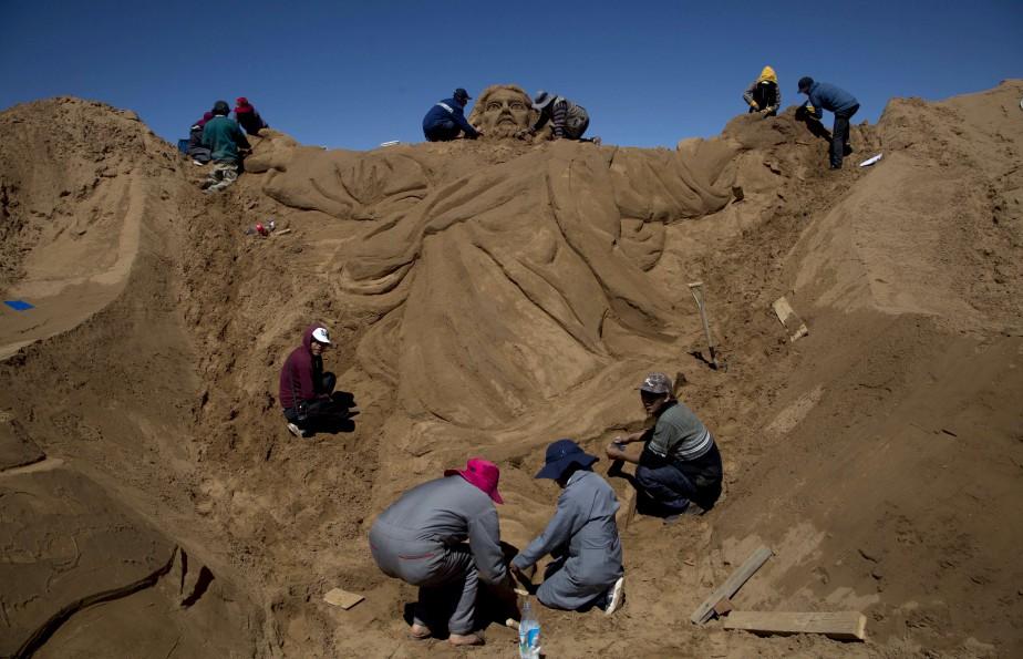 Des artistes travaillent sur une sculpture de sable représentant Jésus Christ, près d'Oruro en Bolivie. | 14 avril 2017