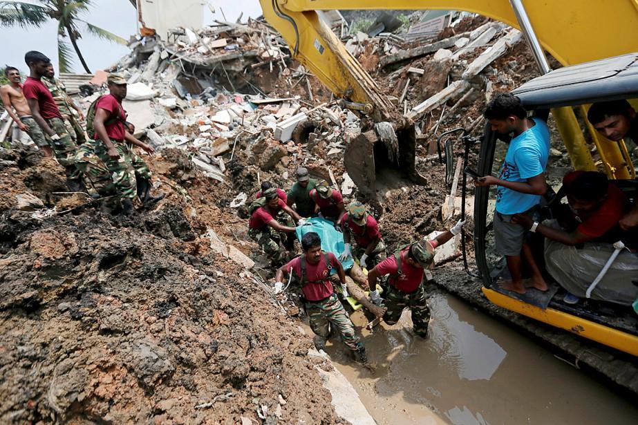 Des militaires transportent le corps d'une victime lors... (Photo Dinuka Liyanawatte, REUTERS)
