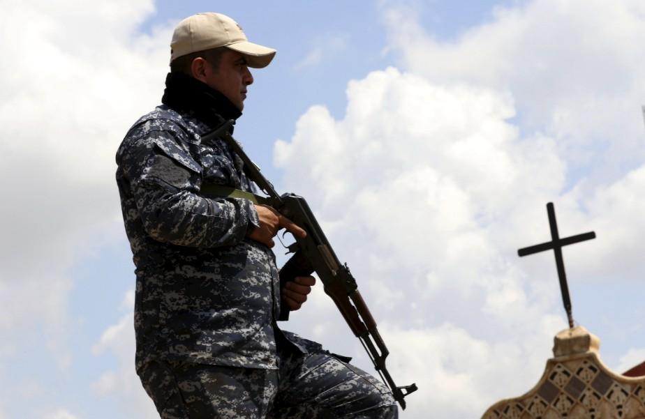 Un membre des forces armées irakiennes faisant la garde devant l'église Mar Shimoni, à Bartella, dans l'est de Mossoul, où est célébrée une messe de Pâques. | 15 avril 2017