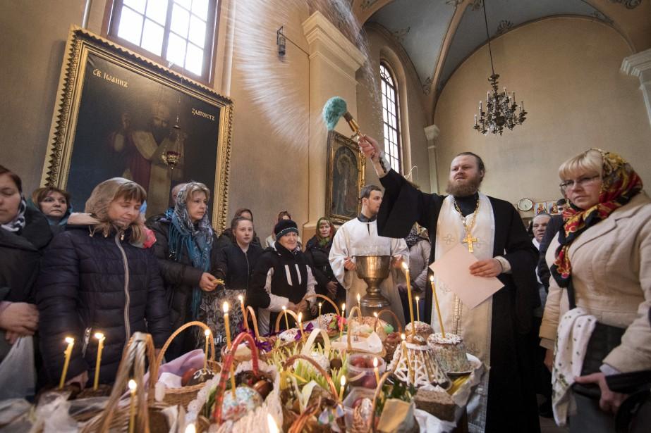 Un prêtre orthodoxe bénissant des oeufs de Pâques et des gâteaux durant une cérémonie orthodoxe de Pâques en Lituanie. | 15 avril 2017