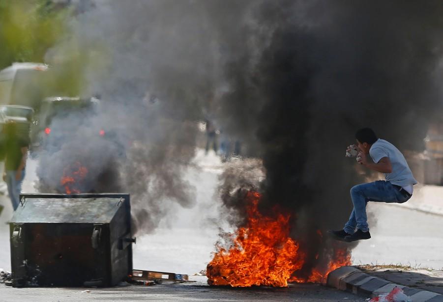 Un manifestant palestinien saute près des pneus brûlés lors des affrontements avec les forces de sécurité israéliennes à la suite d'une manifestation dans la ville de Bethléem en Cisjordanie. | 17 avril 2017