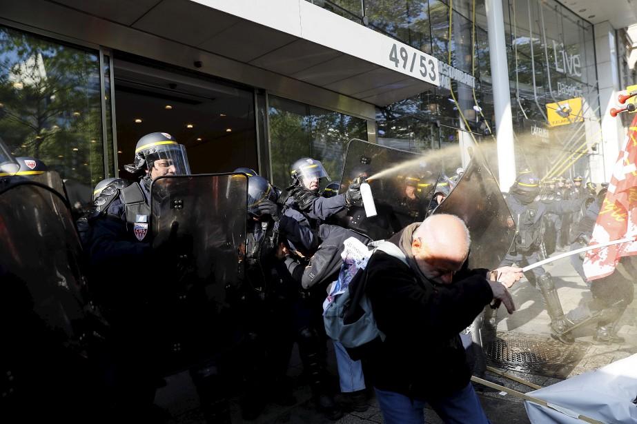 Des policiers français tentent de disperser les manifestants lors d'une manifestation contre les suppressions d'emplois des employés de GM&S aux Champs-Elysées à Paris.   19 avril 2017