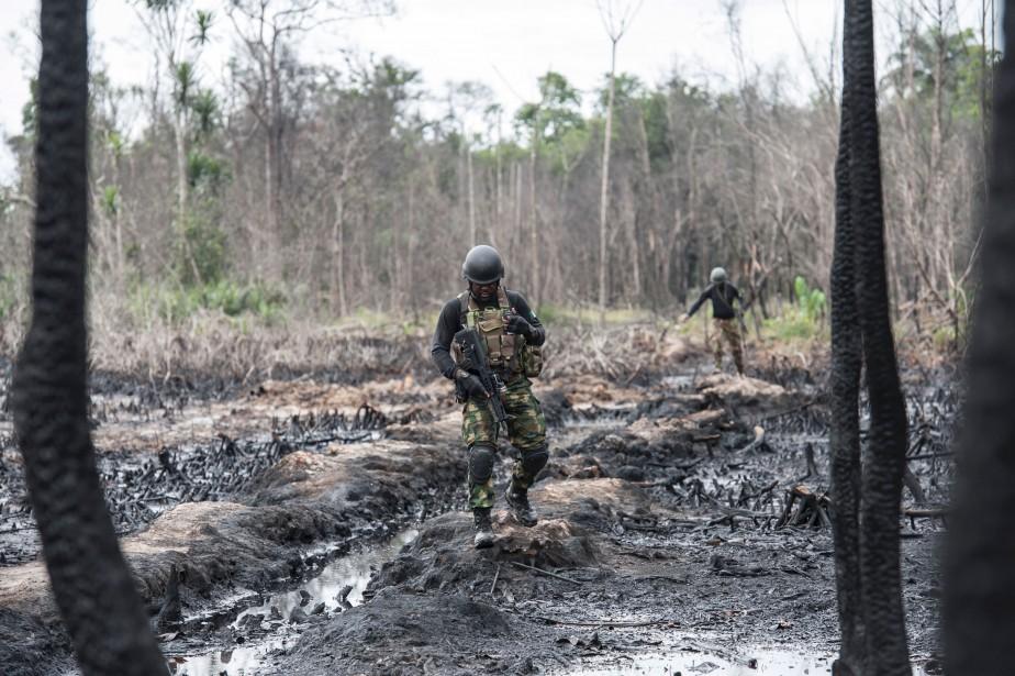Des membres de la Force opérationnelle interarmées traversent un site abandonné d'une raffinerie de pétrole illégale dans la région du delta du Niger. | 20 avril 2017