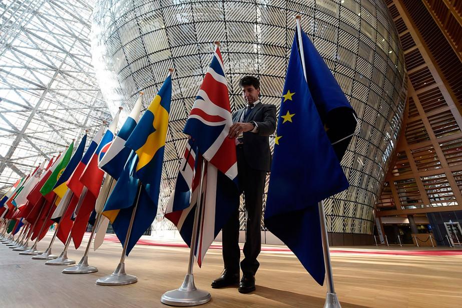 Un organisateur ajuste le drapeau de la Grande-Bretagne... (PHOTO  JOHN THYS, AGENCE FRANCE-PRESSE)