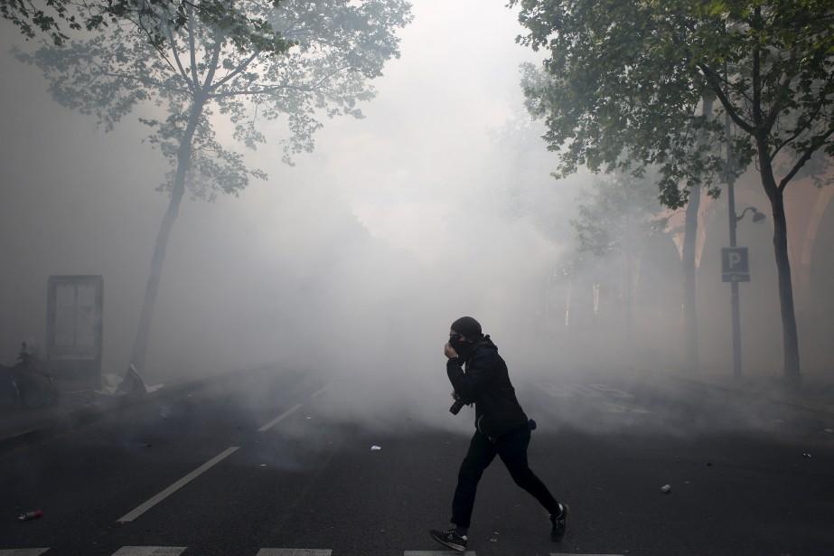 Un jeune manifestant traverse une rue bloquée par un nuage de gaz lacrymogène. | 1 mai 2017