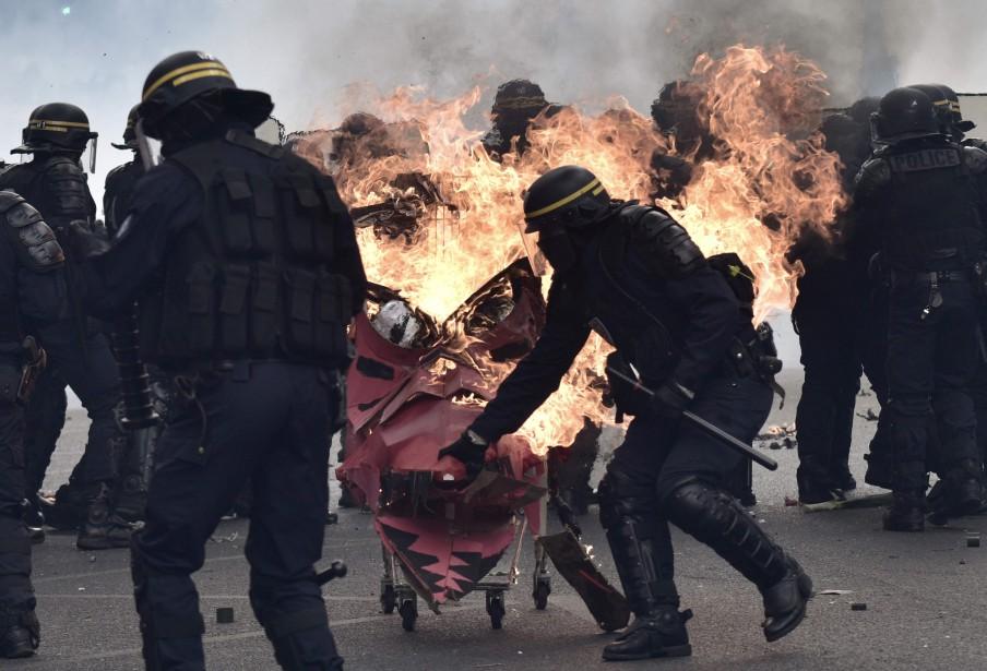 Des policiers tentent de freiner un chariot enflammé propulsé vers eux. | 1 mai 2017