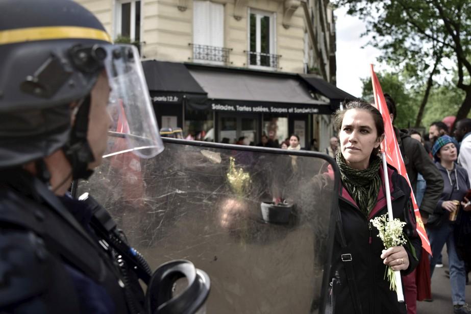 Une femme offre une fleur à un policier anti-émeute. | 1 mai 2017