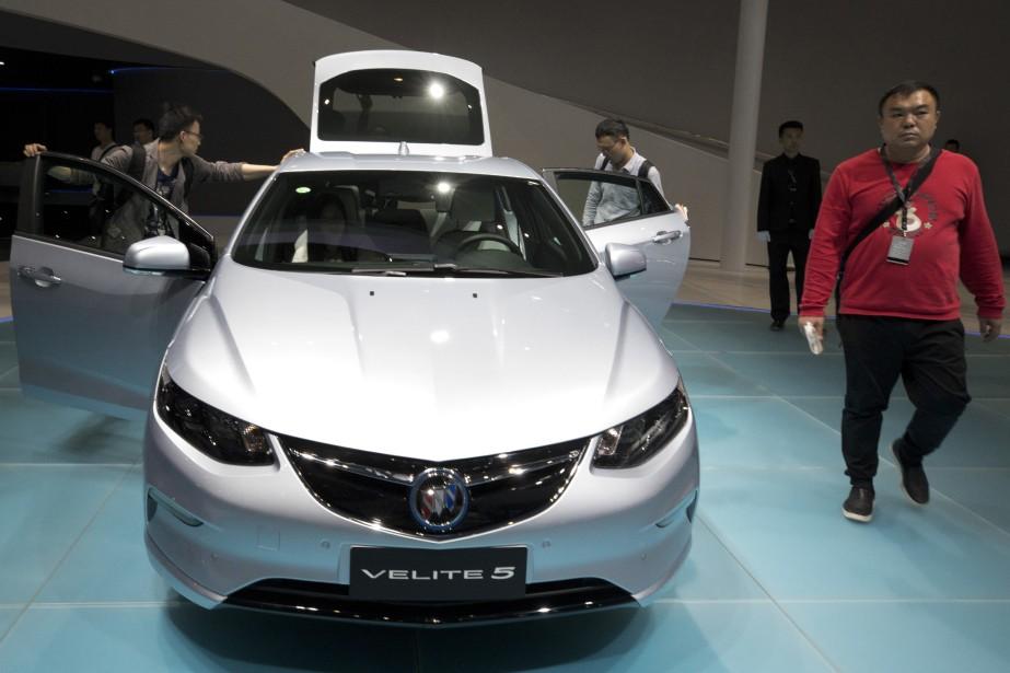 Ce smpathique et souriant chroniqueur automobile passe à côté de l'hybride Buick Velite 5 au Salon de l'auto de Shanghai il y a deux semaines. (photo : AP)