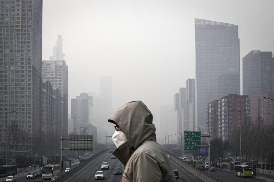 Un homme traverse un passage piétonnier le 6 janvier 2017, alors qu'un smog laiteux flotte sur Pékin. Le smog qui sévit partout en Chine en partie responsable de la présence en grand nombre de touristes chinois dans destinations à l'air pur comme le Canada, l'Islande et l'Antarctique. (La Presse)