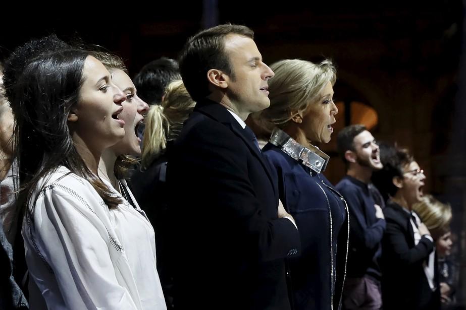 Emmanuel Macron, sa femme Brigitte et leur entourage chantent l'hymne national français lors du rassemblement de la victoire devant le Louvre, à Paris, dimanche soir. | 7 mai 2017