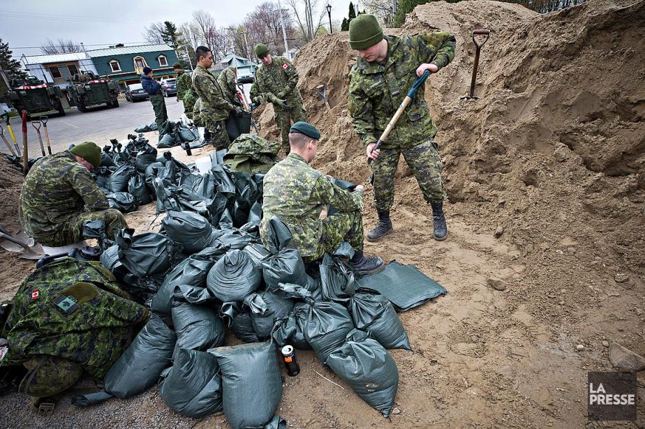 Des militaires remplissent des sacs de sable à... (La Presse, Patrick Sanfaçon)