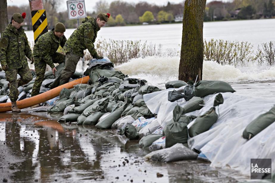 Des militaires prennent soin d'une digue sur la... (Photo Patrick Sanfaçon, La Presse)
