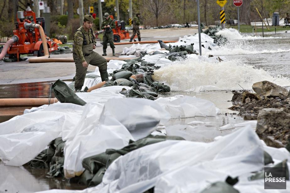 Des militaires surveillent une digue sur la rue... (PHOTO PATRICK SANFACON, LA PRESSE)