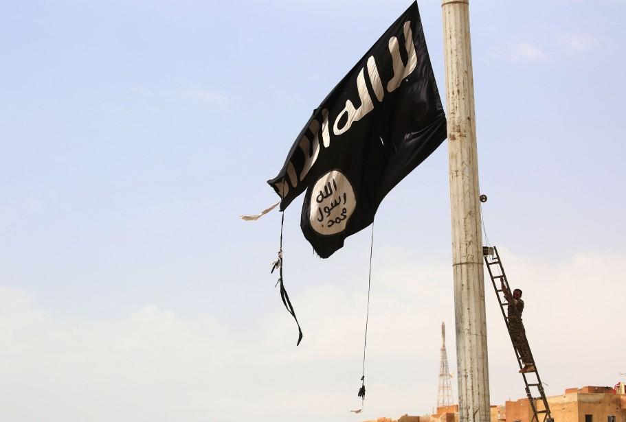 Un membre des Forces démocratiques syriennes décrocha un... (PHOTO AFP)