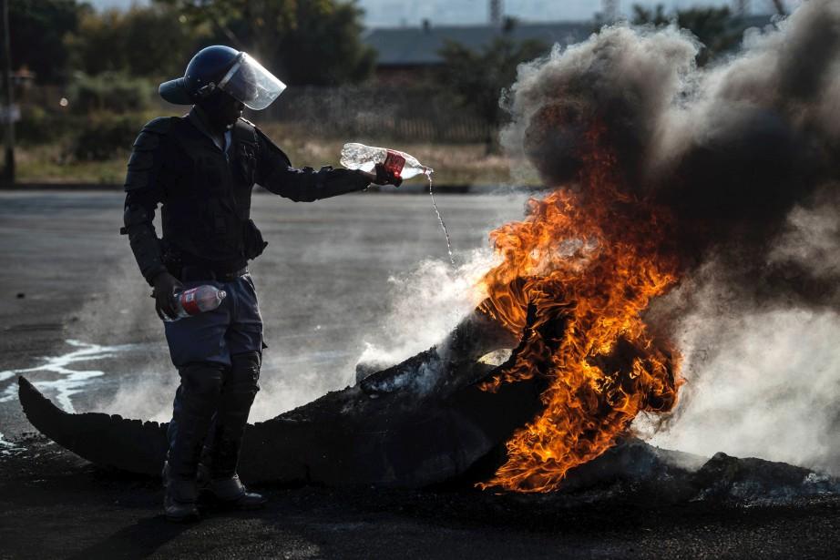 Un policier sud-africain tente d'éteindre un feu de pneus allumé par des manifestants qui ont bloqué une rue durant leurs réclamations pour de meilleures conditions de vie, spécifiquement concernant l'accès au logement. | 11 mai 2017