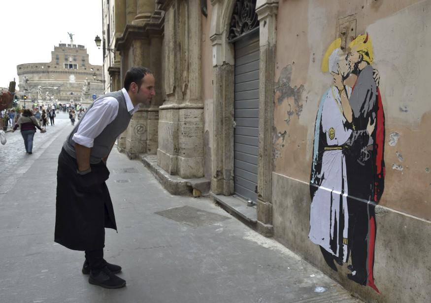 Un serveur observe un graffiti près du Castel Sant'Angelo, à Rome, représentant le pape François et Donald Trump qui s'embrassent avec passion. | 11 mai 2017