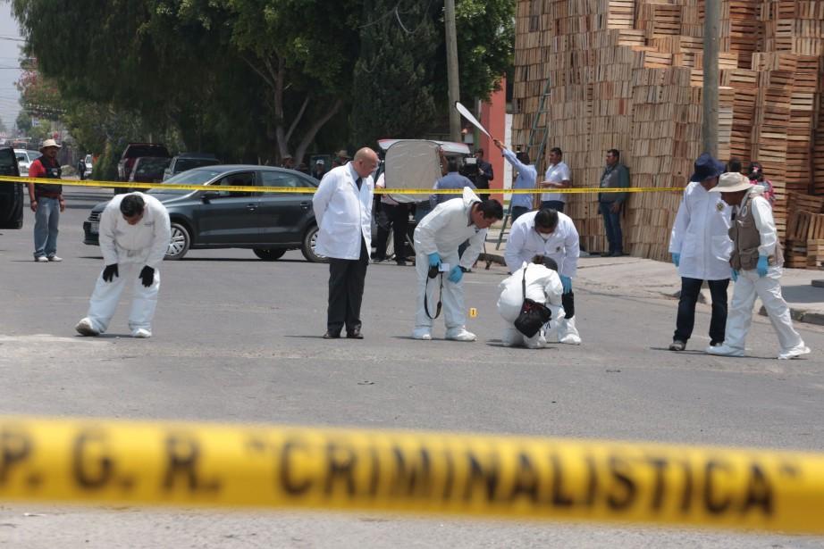Des experts en médecine légale scrutent le lieu... (PHOTO AFP)