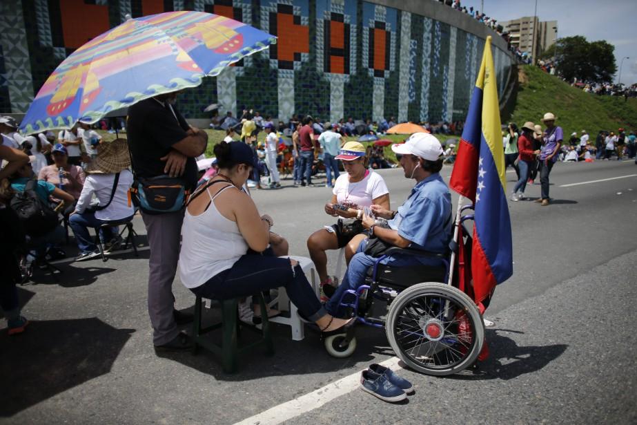 En début-d'après-midi à Caracas, parapluies et capes étaient... (Photo AP)