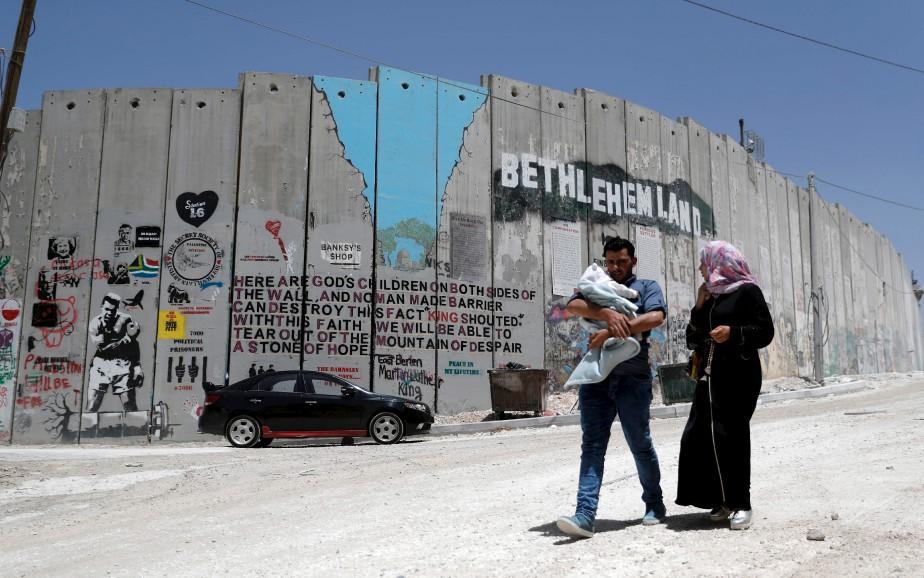 Une famille palestinienne passe devant un graffiti sur le mur controversé séparant l'Israël de la Palestine. | 15 mai 2017