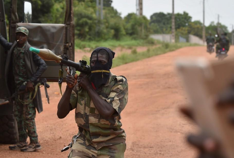 Un soldat de la Côte d'Ivoire tient un lance-roquettes à l'entrée d'un camp militaire à Bouake. Plusieurs soldats menacent le gouvernement d'une mutinerie s'ils se voient refuser les nouvelles conditions de travail demandées. | 15 mai 2017