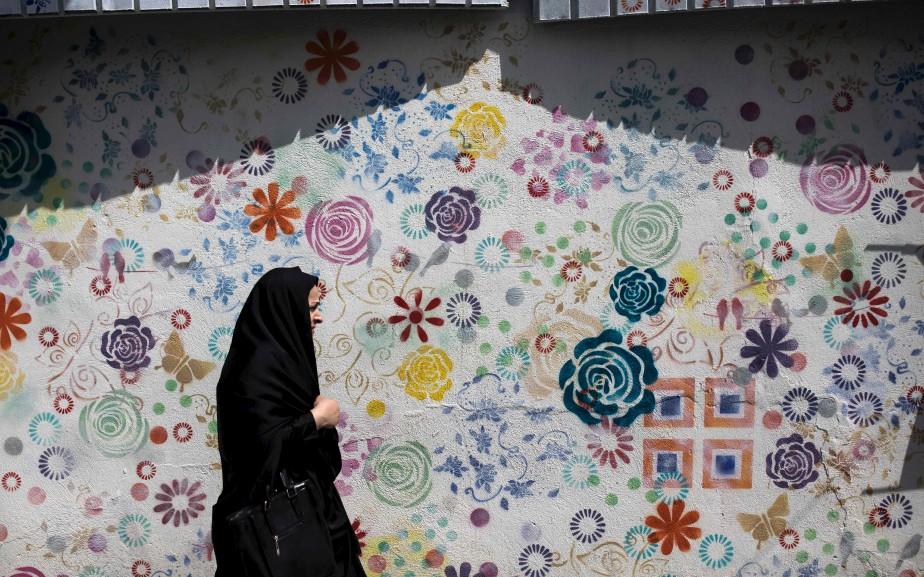 Une Iranienne passe devant un graffiti à Téhéran. Après une série de cuisantes défaites, les conservateurs ont récemment commencé à être actifs sur les réseaux sociaux, un univers auparavant largement dominé par leurs rivaux réformistes. | 15 mai 2017