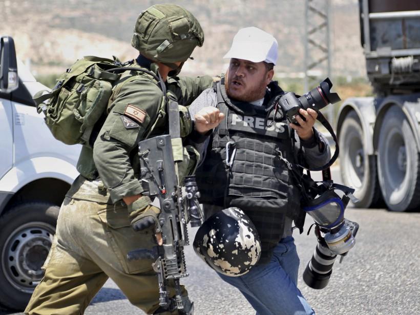 Un soldat israélien bouscule un photographe pendant une grève de la faim par des prisonniers palestiniens, près de la ville de Naplouse. | 16 mai 2017