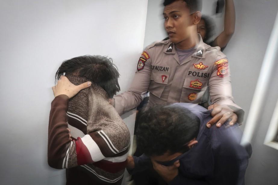Un policier escorte les deux hommes accusés de... (Photo Heri Juanda, Associated Press)