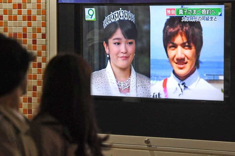 Des passants devant les photos à la télévision... (Photo Hitoshi Takano, Kyodo News via AP)
