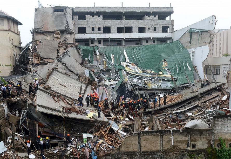 Des pompiers du Sri Lanka fouillent les décombres d'un immeuble de sept étages qui s'est effondré pendant sa construction à Colombo. Plus de vingt travailleurs ont déjà été sortis des décombres et hospitalisés pour des blessures mineures, alors que les autorités continuent de chercher des survivants. | 18 mai 2017