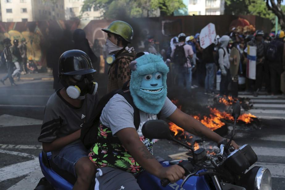 Un manifestant portant un masque à l'effigie du personnage Sulley de Monster Inc. conduit une moto à travers une barricade érigée par d'autres manifestants à Caracas, au Vénézuela.   18 mai 2017