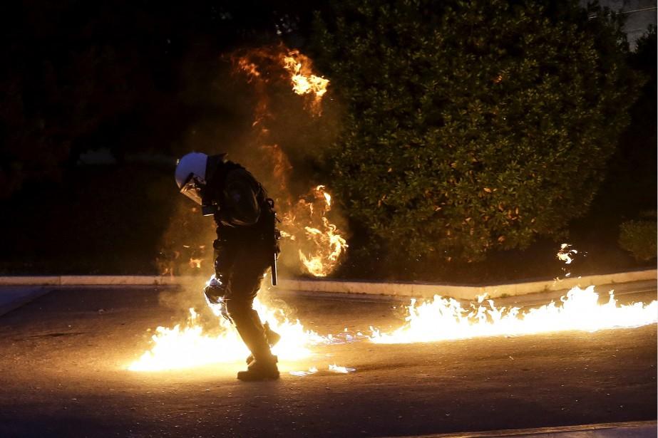 Un policier anti-émeute se fait la cible des cocktails molotov lancés par les manifestants devant le Parlement grec, à Athènes, durant un rallye d'opposition aux mesures d'austérité qui affecteront les revenus des citoyens pour les trois prochaines années.   18 mai 2017