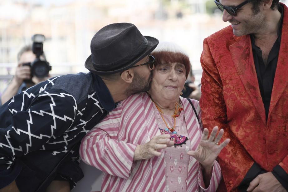 L'artiste français de  streetart  JR embrasse la réalisatrice Agnès Varda sous l'oeil amusé du chanteur Matthieu Chédid. L'équipe présente hors compétition le film  Visages, villages . | 19 mai 2017
