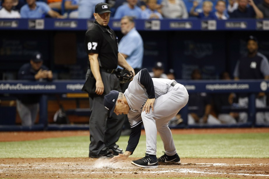 Joe Girardi recouvre le marbre de terre devant... (Photo Kim Klement, USA TODAY Sports)