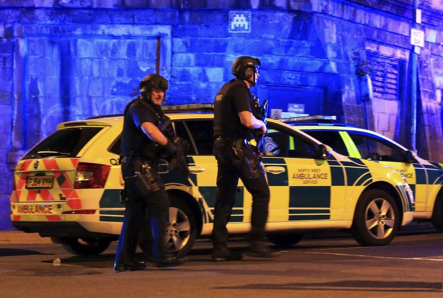 Des policiers armés surveillent les environs de l'amphithéâtre où a eu lieu l'attentat, à Manchester. (AP, Peter Byrne)