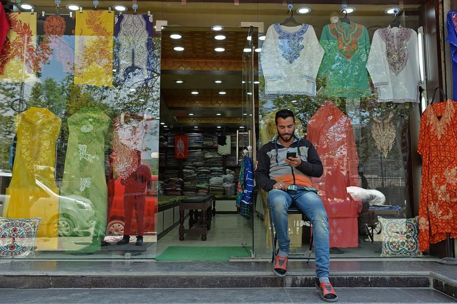 Un homme regarde son téléphone devant son magasin... (PHOTO TAUSEEF MUSTAFA, ARCHIVES AGENCE FRANCE-PRESSE)
