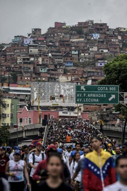 En hommage aux victimes des premières semaines de protestation, la «marche du silence» de l'opposition traverse la capitale jusqu'à l'ouest de Caracas, une zone considérée comme une place forte de l'opposition, généralement inatteignable, car les forces de l'ordre font barrage. La marche parcourt 14km jusqu'au siège de la conférence épiscopale vénézuélienne, après une médiation des religieux avec les militaires. -PHOTO AFP, Federico PARRA | 2 juin 2017