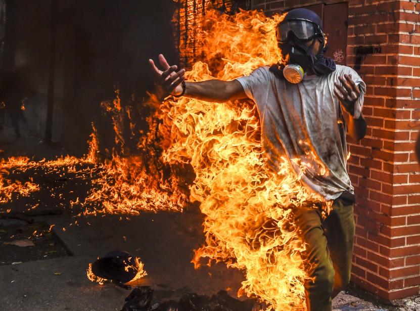 Victor Salazar, 28ans, se transforme en torche humaine après avoir été touché par l'explosion du réservoir d'une moto militaire qu'il vient d'incendier avec d'autres manifestants, le 3mai à Caracas. «Le jeune courrait vers moi, enveloppé dans les flammes. Je ne pouvais pas l'aider. Je ne pouvais que montrer» l'horreur de la scène, raconte Juan Barreto. Le manifestant a survécu, le corps brûlé à 70%. | 2 juin 2017