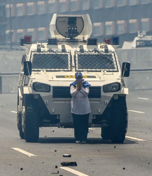Enveloppée dans un drapeau jaune, bleu et rouge vénézuélien, Maria José Castro, 54ans, bloque pendant de longues minutes l'avancée d'un véhicule blindé de l'armée, le 19avril dans la capitale. Les militaires tentent de la dégager à l'aide de grenades lacrymogènes. Mais elle reste ferme, le visage couvert d'un foulard, sourde aux injonctions du mégaphone. C'est finalement une moto militaire qui l'évacuera. Elle sera relâchée quelques heures plus tard. | 2 juin 2017